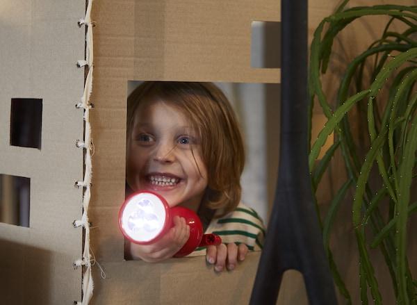 """Uma menina feliz no jogo do """"cucu"""" e a segurar uma lanterna LED manual LJUSA em vermelho."""