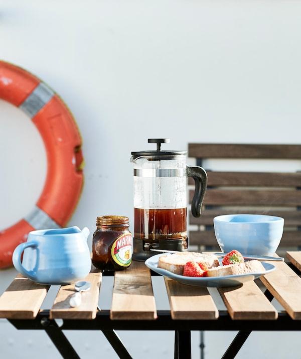 Uma mesa de exterior posta para o pequeno-almoço, com uma boia salva-vidas em laranja em segundo plano.