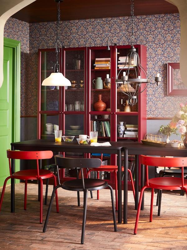 Uma mesa de refeição TOMMARYD combinada com cadeiras YNGVAR em cores variadas, em frente a duas vitrinas em vermelho.