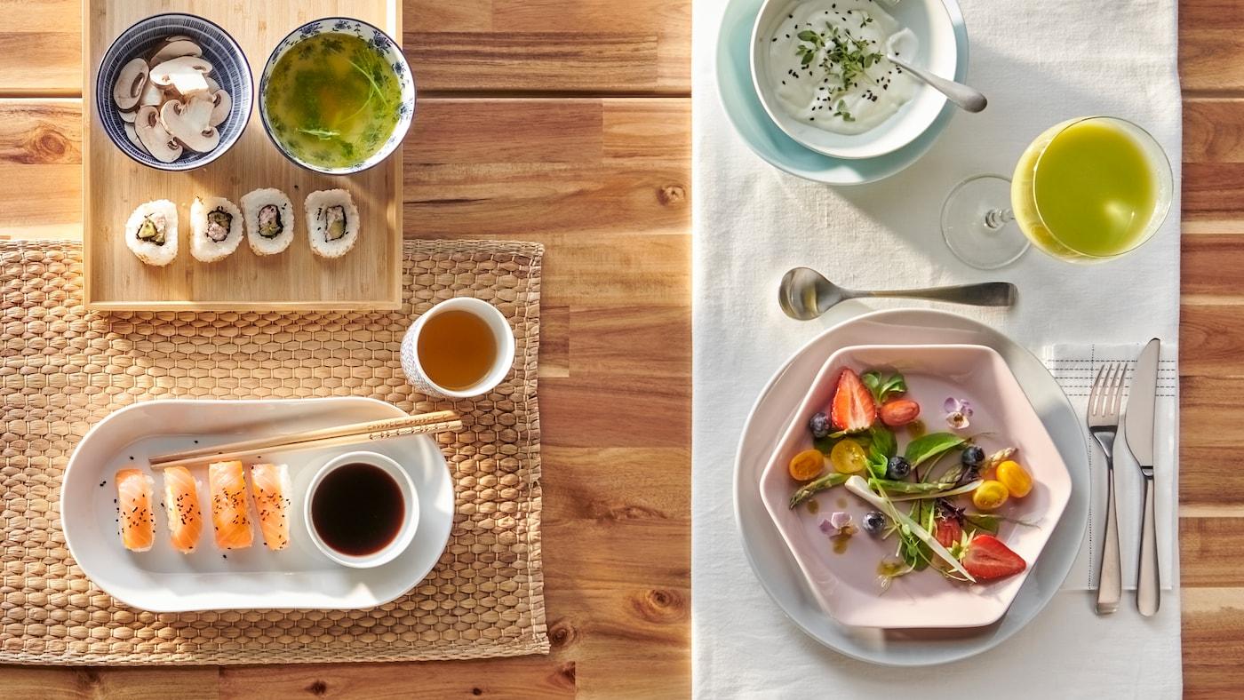 Uma mesa posta de duas maneiras: uma para sushi num prato branco oval, outra para uma salada num prato rosa hexagonal.