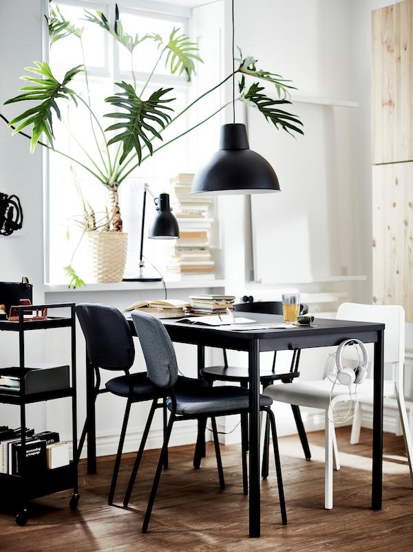 Uma mesa TOMMARYD em preto com quatro cadeiras diferentes em branco, cinzento e preto, candeeiros pretos e uma grande planta no parapeito.