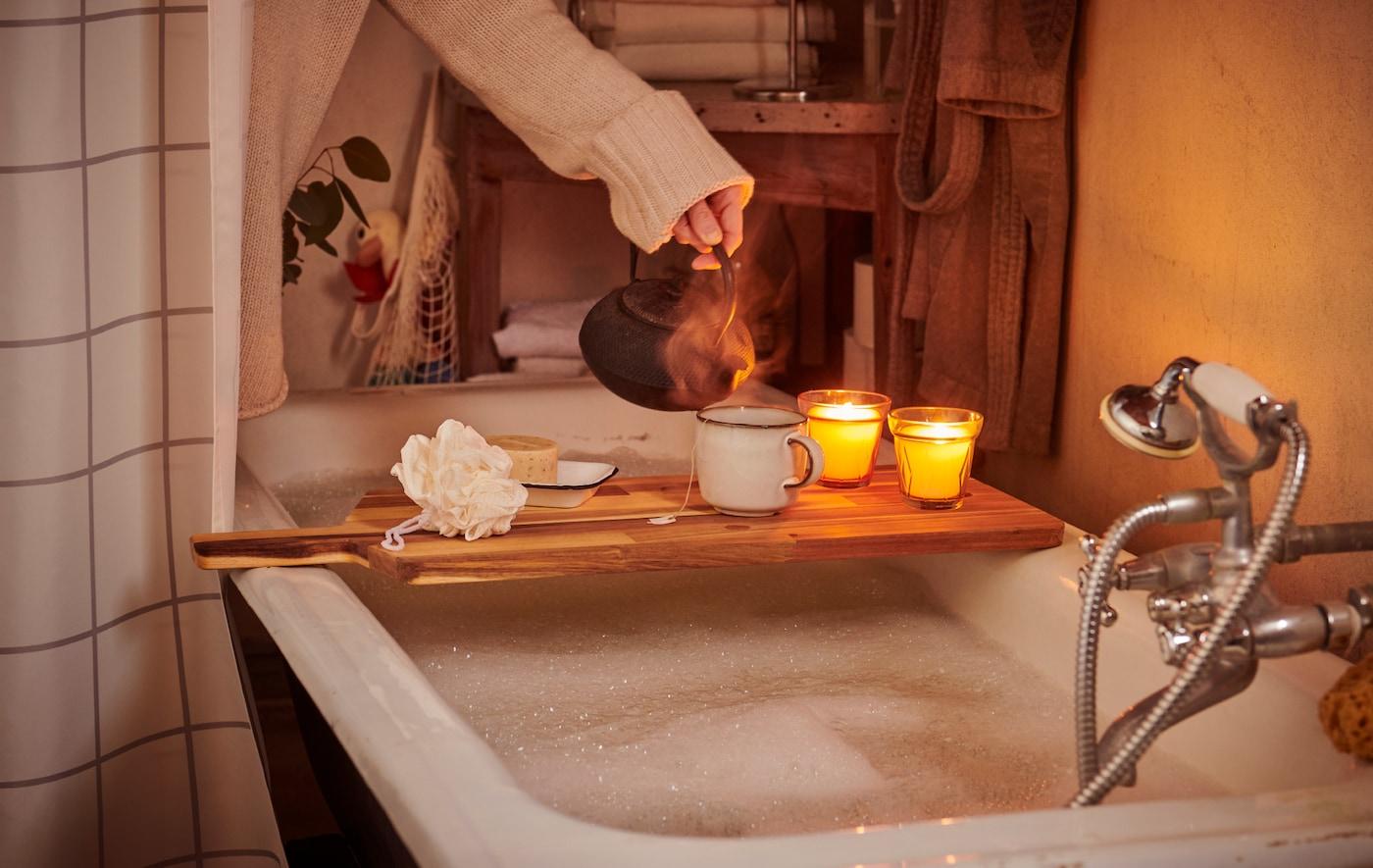 Uma mulher, com uma camisola vestida, a preparar um dia de spa, verte chá para uma chávena pousada sobre uma tábua de cortar, colocada sobre uma banheira.