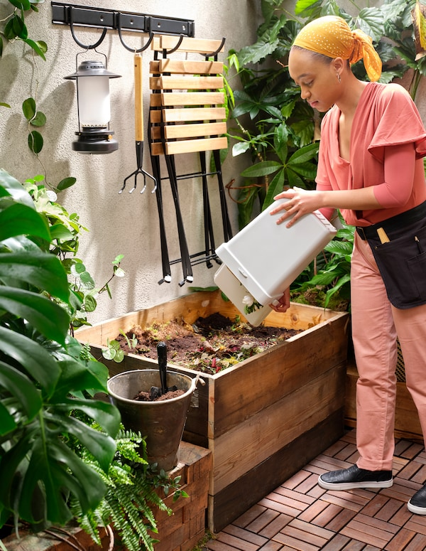 Uma mulher despeja o desperdício alimentar que se encontra num caixote HÅLLBAR branco para um contentor de madeira para compostagem, num quintal pequeno com deck de madeira e muitas plantas.