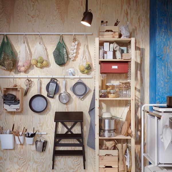 Uma parede de madeira onde estão instaladas calhas em branco com ganchos: aqui estão pendurados sacos com fruta, utensílios de cozinha e um banco com degraus.