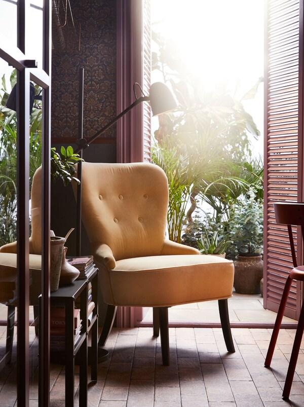 Uma poltrona REMSTA em amarelo junto a uma porta aberta para um terraço com plantas. Um candeeiro de pé e uma mesa em preto com livros ao lado da poltrona.