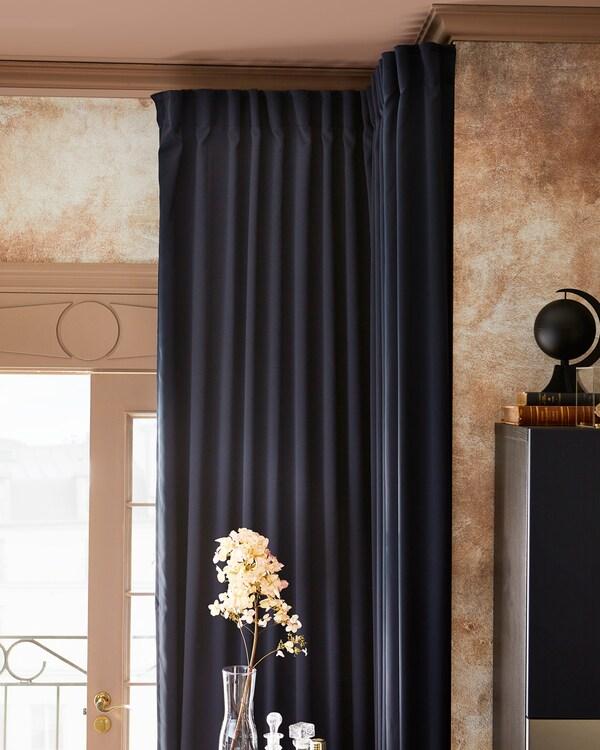 Uma sala com cortinados opacos MAJGULL em azul escuro, abertos para deixar entrar a luz, e um ramo de flores numa jarra de vidro.