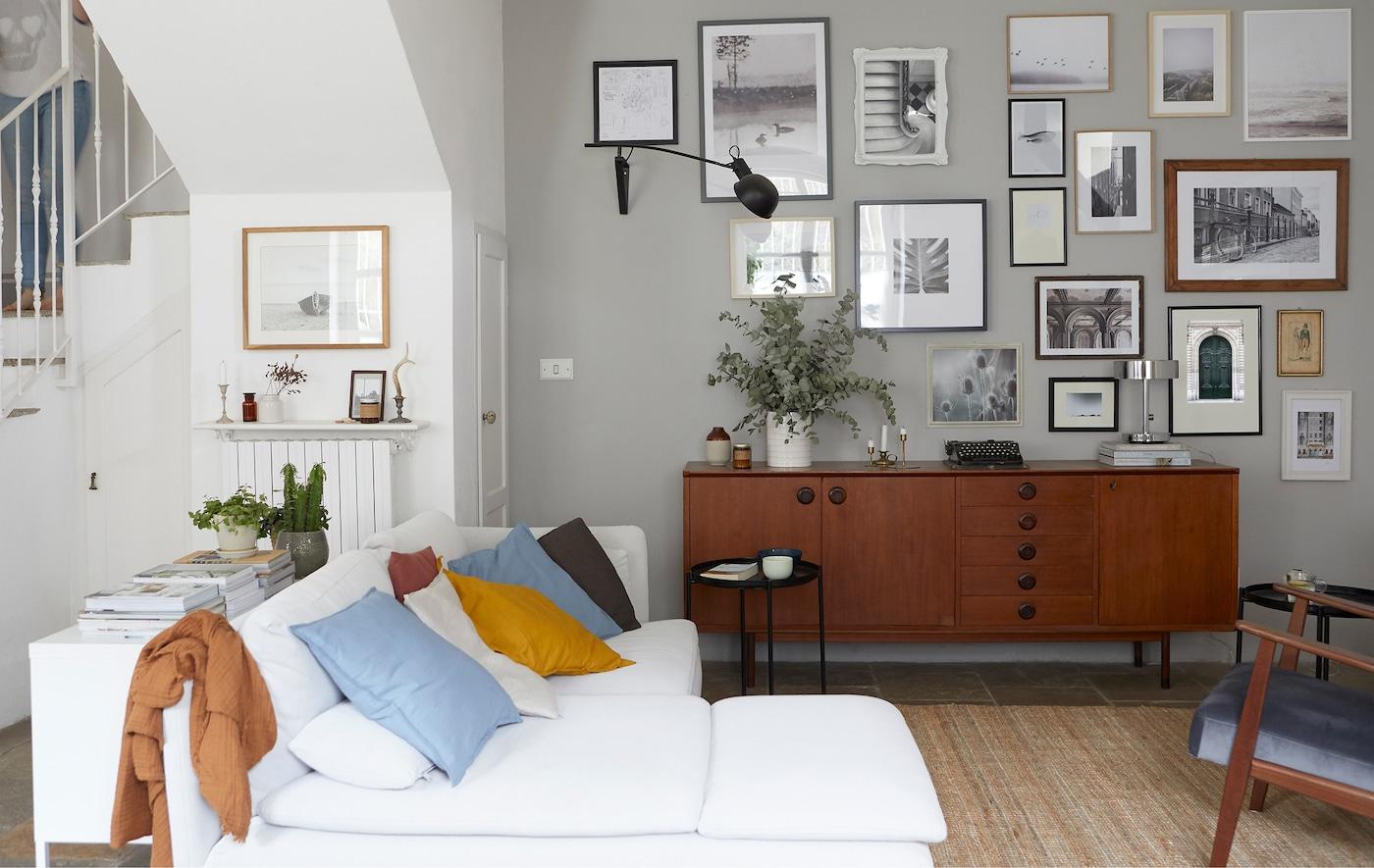 Uma sala com um sofá de canto em branco, um aparador em madeira escura e uma galeria de imagens na parede.
