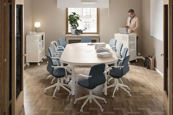 Uma sala de reuniões com uma mesa de reuniões e 10 cadeiras. Um homem de pé ao fundo, junto a uma janela, a trabalhar num computador sobre um armário.