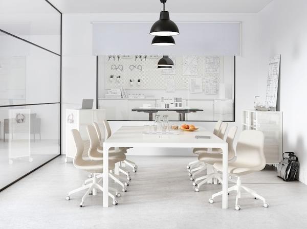 Uma sala de reuniões com uma parede envidraçada e uma mesa branca grande. Uma fila de candeeiros suspensos SKURUP pendurados no teto.