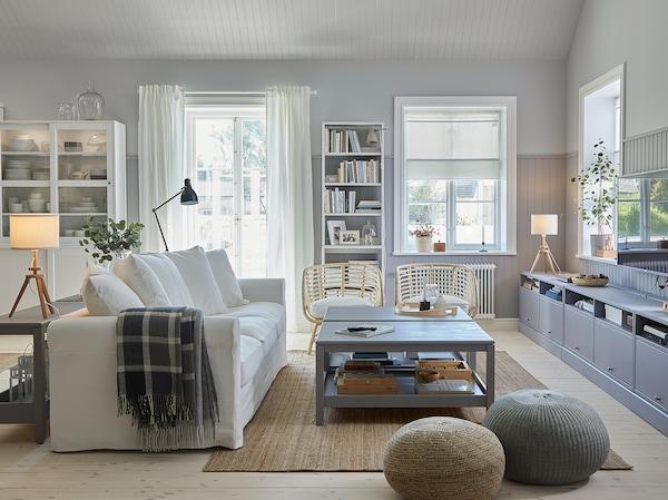Uma sala tradicional com um sofá em branco, um tapete em juta, duas mesas de centro em cinzento, um móvel de TV em cinzento e duas poltronas em rota.