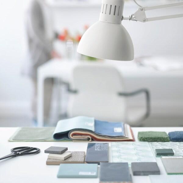 Uma secretária com amostras de cores em tons de verde e azul e um candeeiro de secretária branco.