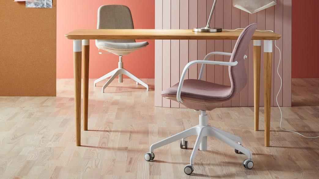 Uma secretária em bambu e duas cadeiras de escritório LÅNGFJÄLL de cores e modelos diferentes.