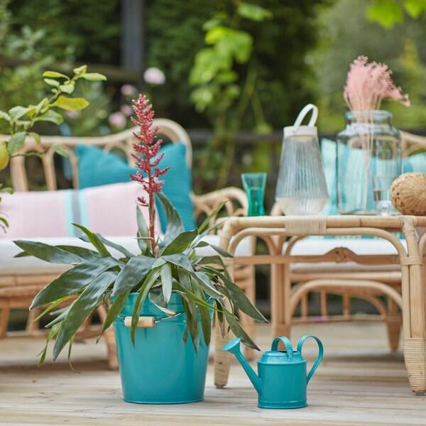 Uma varanda com móveis em verga, destacando um balde e regador azuis turquesa
