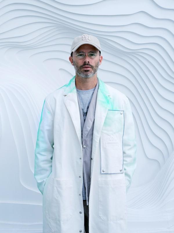 Umělec Daniel Arsham oblečený do bílého pláště potřísněného tyrkysovou barvou stojí před šedou stěnou.