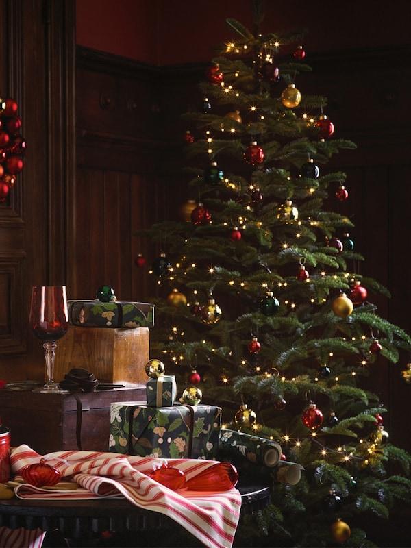 Umělý vánoční stromek se světýlky ozdobený zlatými ozdobami ve tvaru chaloupek a červenými koulemi.