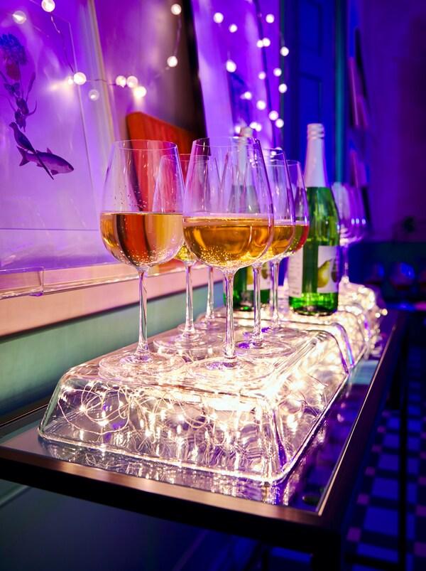 Umgedrehte MIXTUR Ofenformen aus Klarglas mit einer VISSVASS Lichterkette darunter. Auf der Ofenform sind Weingläser zu sehen.