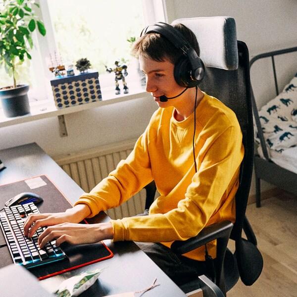 Un adolescent assis dans sa chambre sur une chaise JÄRVFJÄLLET à une table LINNMON/ALEX, portant un casque d'écoute, est en train d'utiliser un ordinateur.