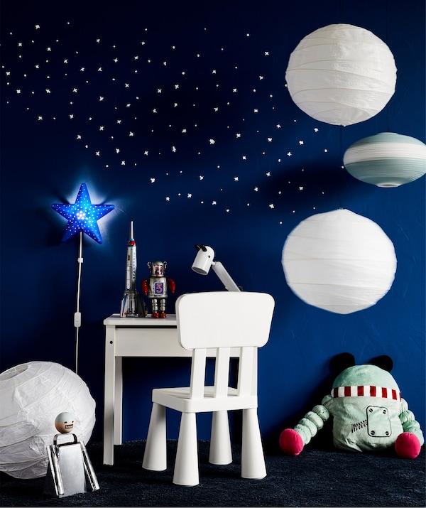 Un ambiente de trabajo inspirado en el espacio con un escritorio infantil IKEA SUNDVIK en color blanco, una silla blanca y lámparas de papel de arroz blancas.