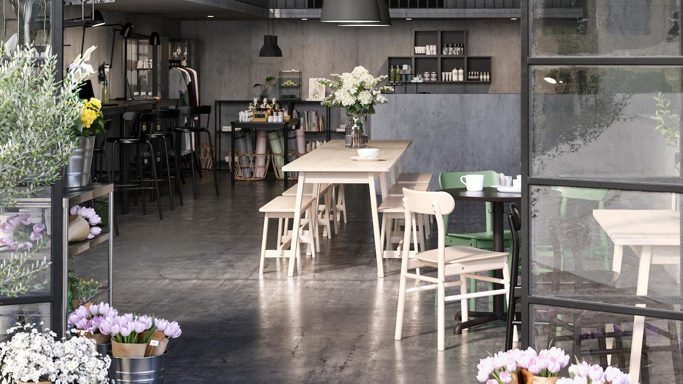 Un ambiente open space delimitato da porte a vetro, con postazioni di co-working, bar e negozio. Un vaso di fiori sul tavolo al centro dello spazio e altri fiori vicino alle porte.
