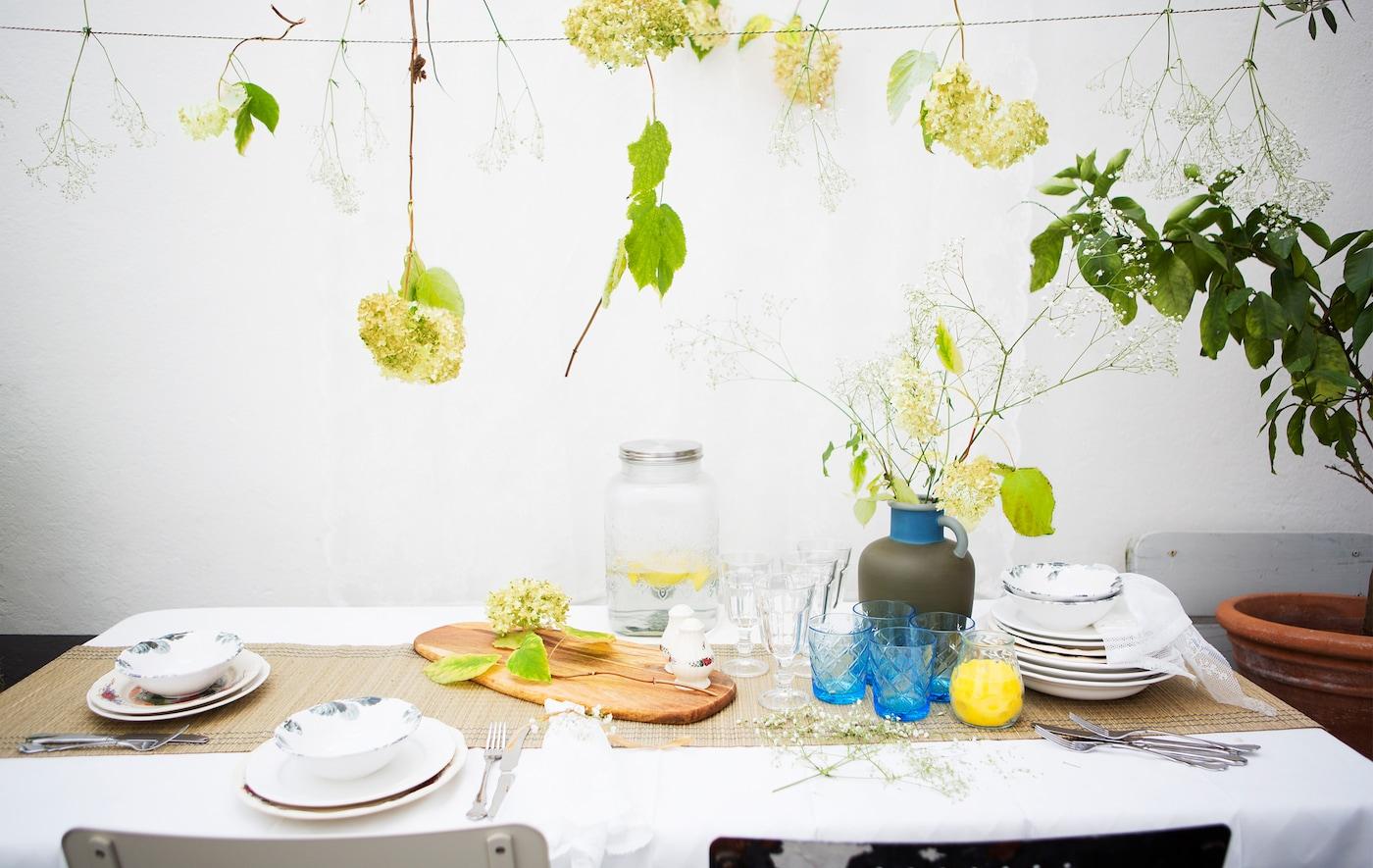 Un aranjament de masă cu vase ceramice cu model, pahare și o vază cu flori, și flori suspendate.