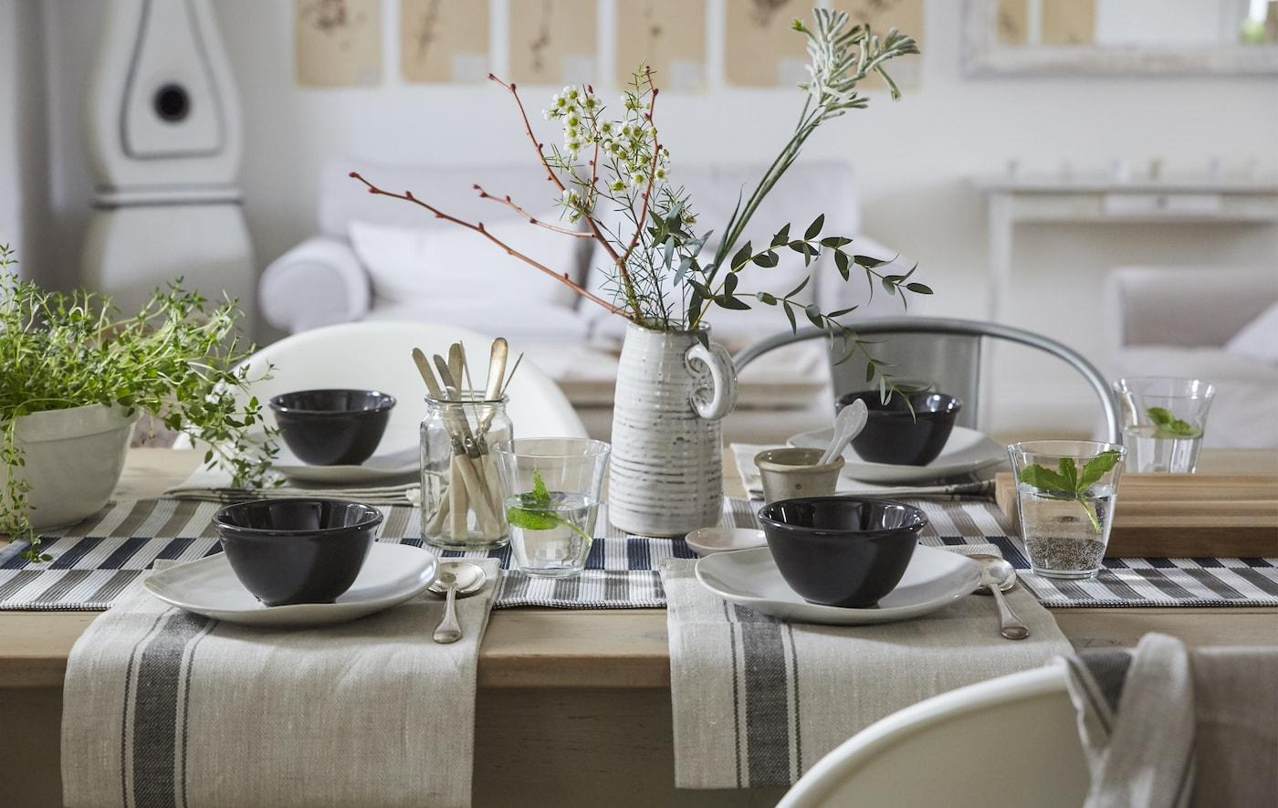 Un aranjament de masă în culori neutre cu prosoape de masă din bumbac, aranjamente simple pentru luat masa și un aranjament central natural.