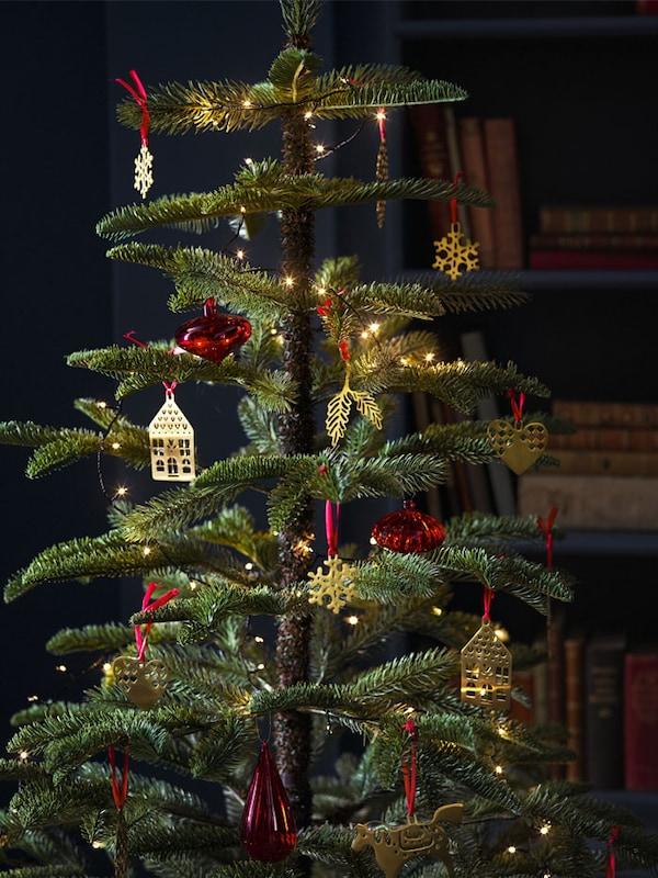 Un arbre de Noël artificiel garni de lumières et d'ornements dorés en forme de maisons et de boules rouges.