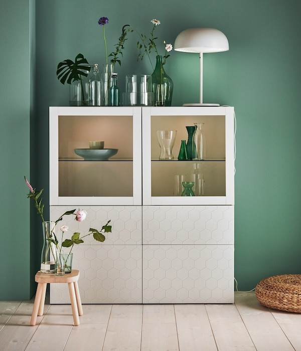 Un armadio per soggiorno con vetrina illuminata e ante chiuse in bianco.