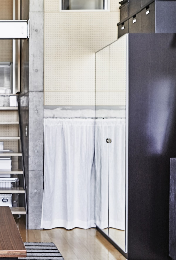Un armari amb mirall al costat d'unes escales.
