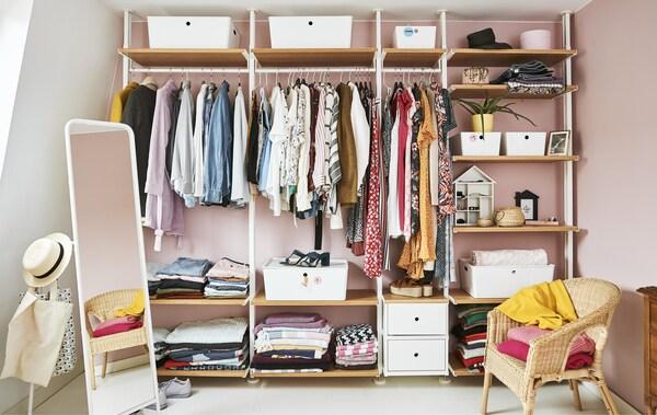 Un armario abierto lleno de ropa con rieles, estantes y cajas contra una pared rosa.