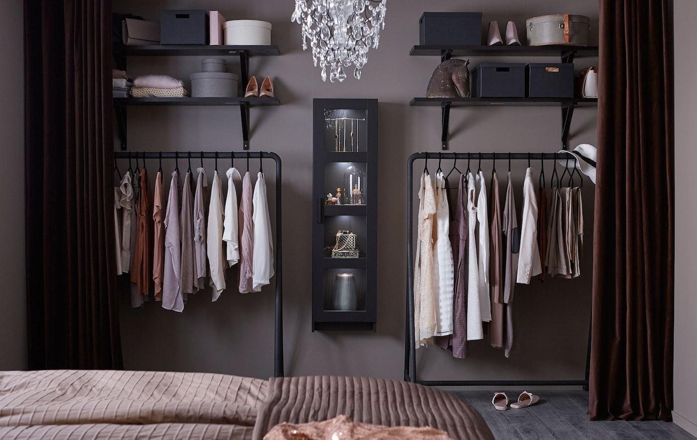 Un armario abierto que incluye percheros negros, estantes abiertos negros y una vitrina negra, llena de ropa.