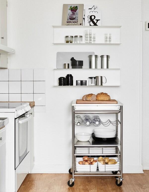 Un armario de armario aberto onde colocar os libros de cociña e colectores de alimentos e un carriño de aceiro inoxidable debaixo ofrece un espazo flexible.