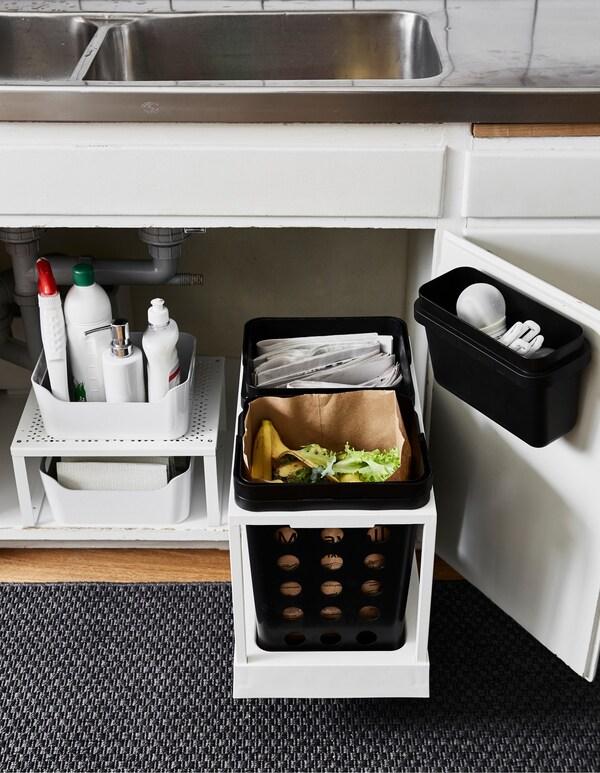 Un armario de cociña branco debaixo do vertedoiro, aberto para amosar dous cubos negros utilizados para reciclaxe e lixo.