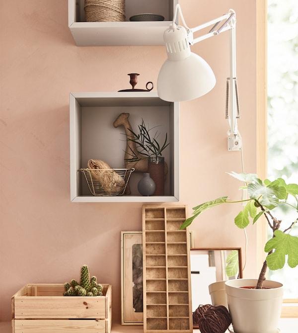 Un armario EKET cuadrado gris montado en la pared de un salón rosa y utilizado para guardar y mostrar los artículos favoritos.