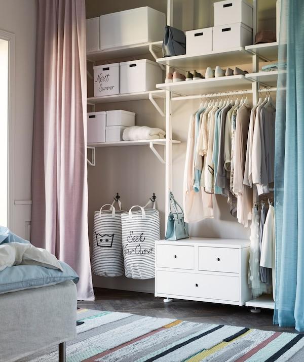 Un armario ELVARLI lleno con una cortina azul y rosa en cada lado.