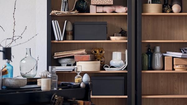 Un armario HEMNES cheo de cerámicas, libros, caixas de almacenaxe e outros obxectos.