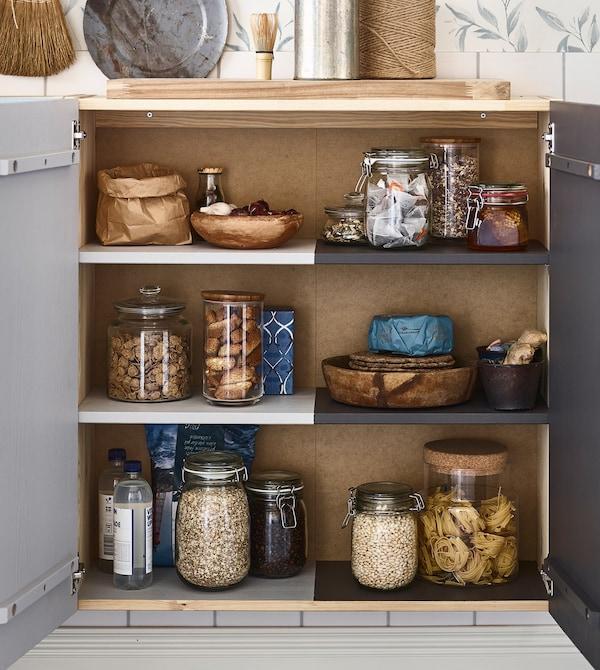 Un armario IVAR de IKEA con tarros de almacenamiento con comida seca pintado para mostrar quién es el propietario de cada parte.