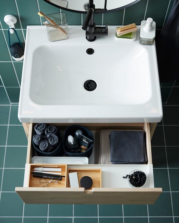 Un armario/lavabo en bidueiro/branco cun caixón aberto. As toallas e a maquillaxe están organizadas en bandexas e cestas.