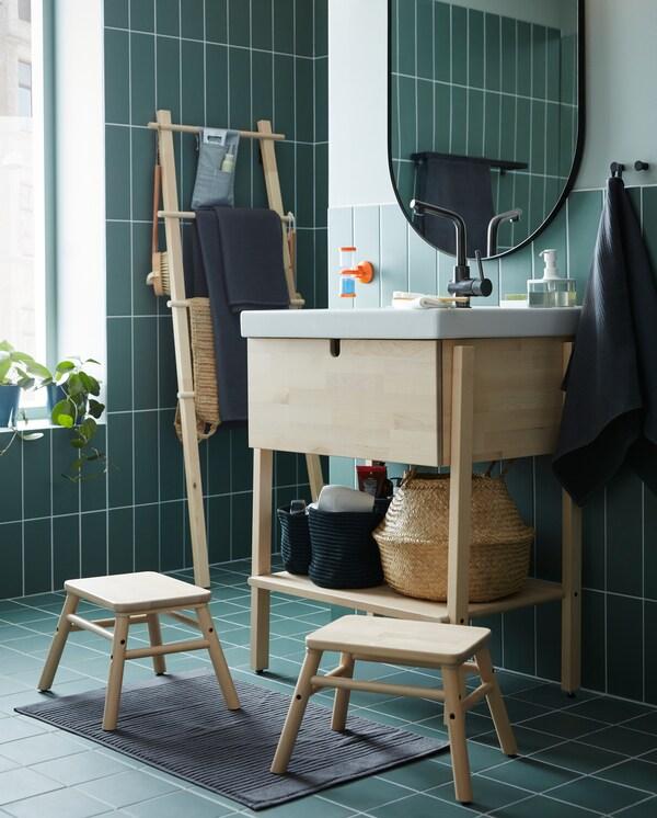 Un armario/lavabo en bidueiro/branco, dous tallos chanzo en bidueiro, un espello ovalado e unha toalla de man en gris escuro.