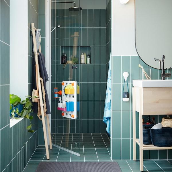 Un armario/lavabo en bidueiro/branco, un espello ovalado, un toalleiro en bidueiro, tres cestas azuis e unha porta de cristal para a ducha.