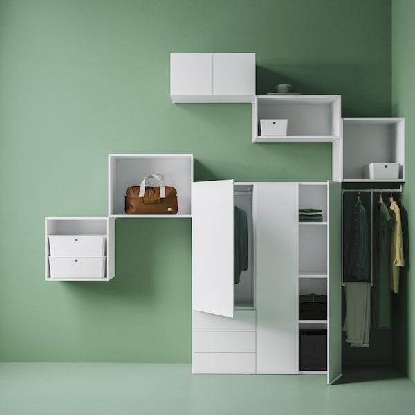 Un armario y estructuras PLATSA montadas en la pared en una habitación verde, junto con algunas cajas y ropa colgando de una barra.