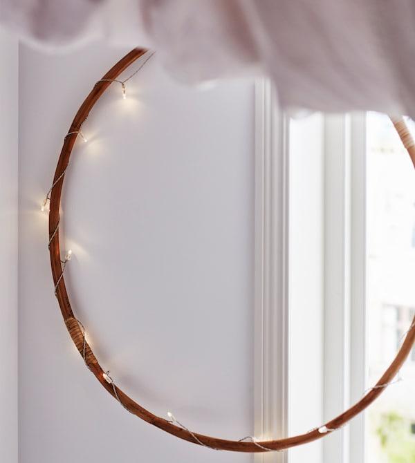 Un aro de madera está rodeado de una tira de luces y cuelga de la pared, parcialmente delante de una ventana.