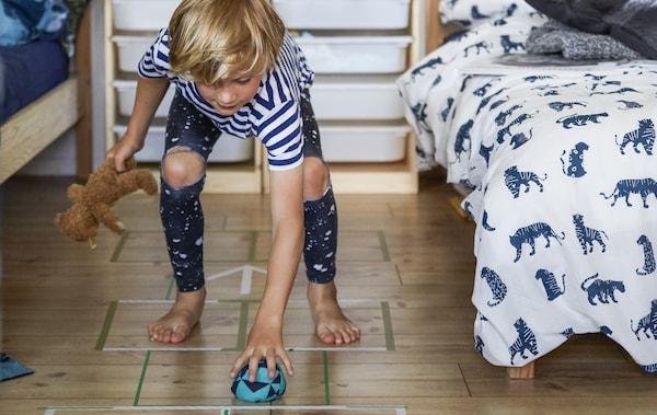 Un băiat jucând șotronul pe parchetul din lemn dintre două paturi.