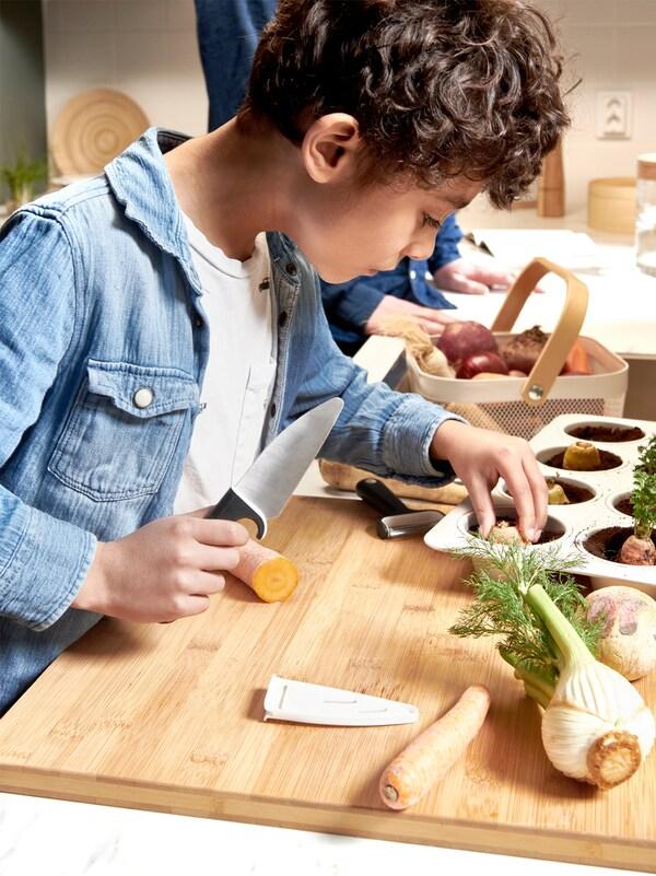 Un băiețel care ține un cuțit în mână și așază un capăt de morcov înfrunzit într-o tavă de copt plină cu pământ, pe o suprafață din lemn, cu alte legume.