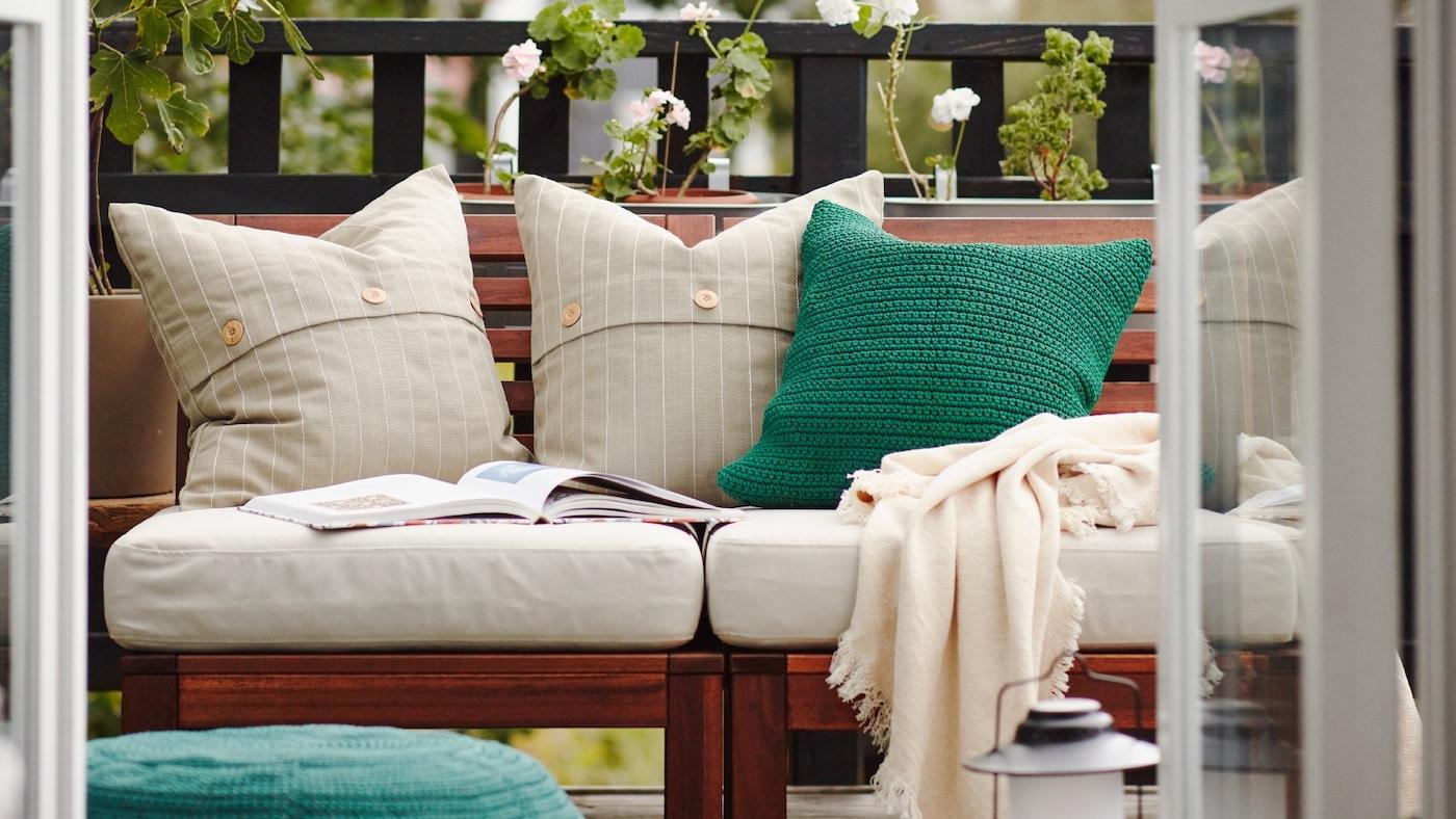 Un balcon avec canapé d'extérieur en bois aux coussins blancs et verts, un jeté et un livre ouvert, et des plantes vertes derrière.