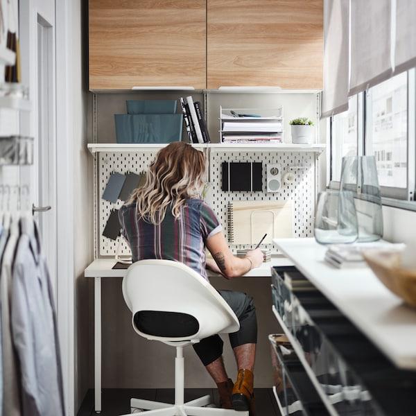 Un balcon avec une baie vitrée et une personne qui travaille dans un bureau à la maison, avec des armoires et des tablettes murales.