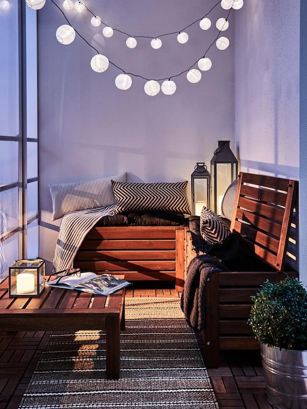 Un balcon cu mobilier de exterior din lemn cu perne, lămpi, ghirlande de lumină și o plantă.