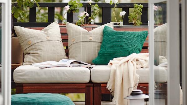 Un balcon cu o canapea de exterior din lemn cu perne albe și verzi, un taburet cu o carte deschisă pe el, plante verzi în spate.