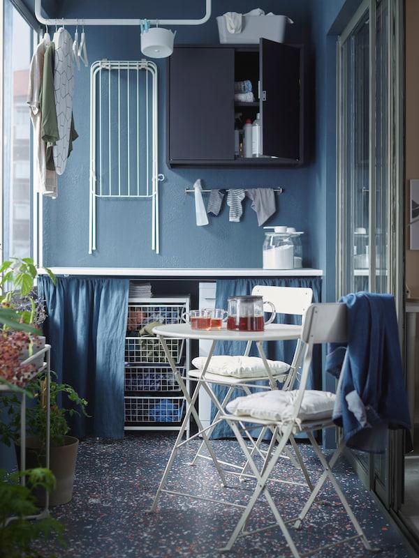 Un balcon cu o masă albă și două scaune, un uscător pliabil agățat pe perete și câteva plante.