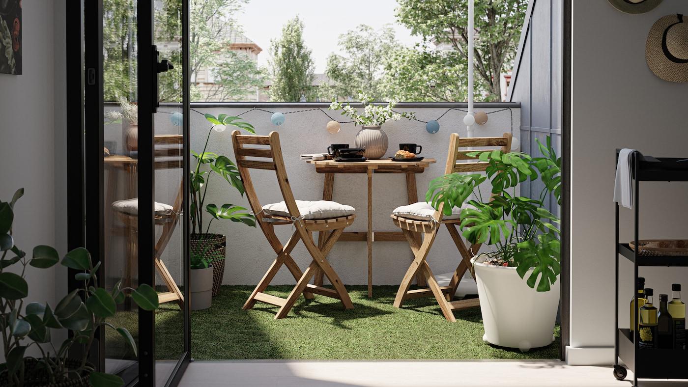 Un balcón pequeño con una mesa de madera y sillas, suelo de césped artificial y una planta monstera en un macetero blanco.
