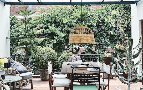 Un balcone con piante, sedie, tavolo e una lampada a sospensione - IKEA